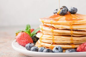 Close-up delicious pancakes, with fresh blueberries, strawberries and maple syrup on a light background. With copy space. Sweet maple syrup flows from a stack of pancake.